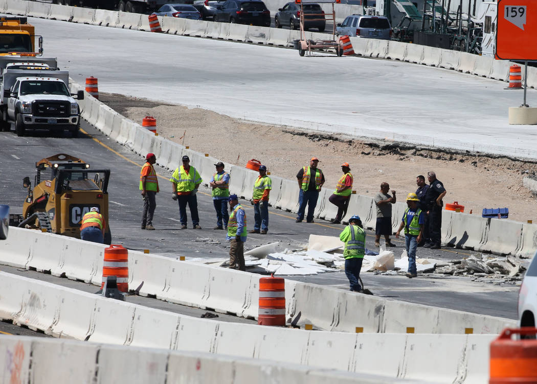 Workers remove debris after a crash involving a tractor trailer just north of the Spaghetti Bowl on Thursday, May 10, 2018, in Las Vegas. Bizuayehu Tesfaye/Las Vegas Review-Journal @bizutesfaye
