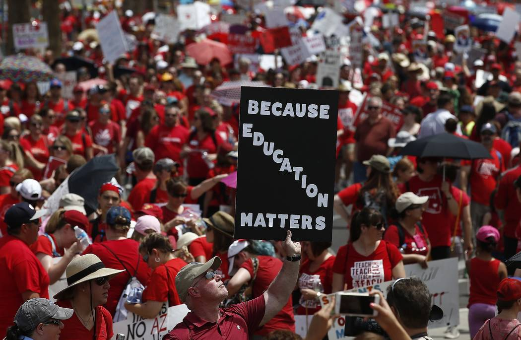 Thousands march to the Arizona Capitol for higher teacher pay and school funding Thursday, April 26, 2018, in Phoenix. (AP Photo/Ross D. Franklin)