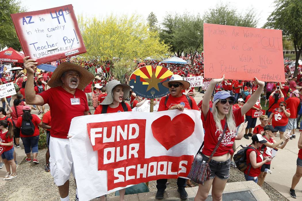 Thousands chant as they participate in a protest at the Arizona Capitol for higher teacher pay and school funding on the first day of a state-wide teachers strike Thursday, April 26, 2018, in Phoe ...