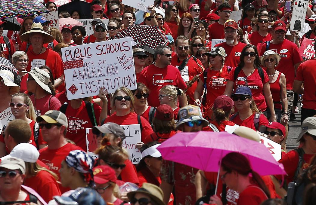 Thousands march to the Arizona Capitol for higher teacher pay and public school funding on the first day of a state-wide teachers strike Thursday, April 26, 2018, in Phoenix. Arizona leaders deali ...