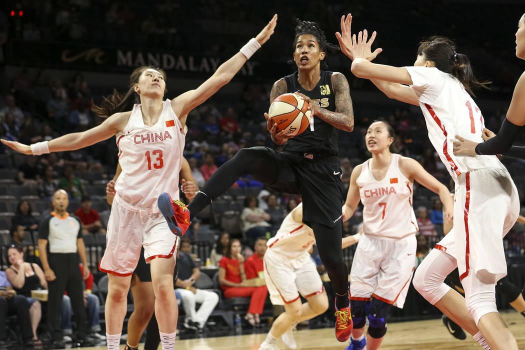 Las Vegas Aces forward Tamera Young (1) gets fouled by China's Mengran Sun (13) and Zhengi Pan (17) during a preseason basketball game at Mandalay Bay Events Center in Las Vegas on Sunday, May 6, ...