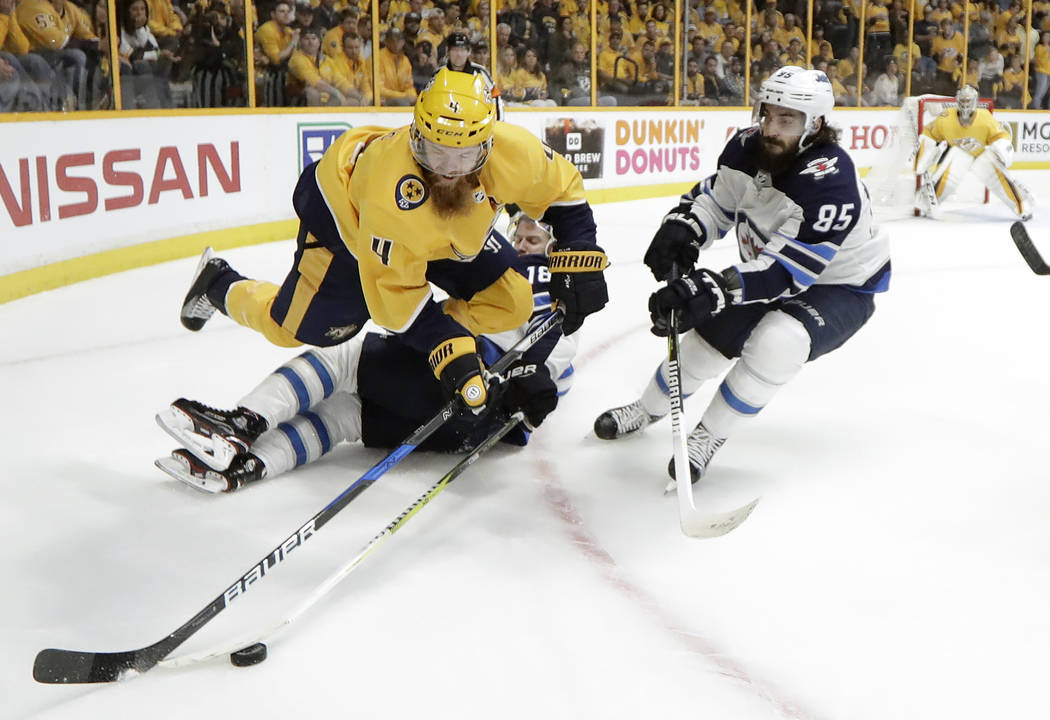 Nashville Predators defenseman Ryan Ellis (4) jumps over Winnipeg Jets' Bryan Little (18) as Mathieu Perreault (85) closes in during the first period in Game 7 of an NHL hockey second-round playof ...
