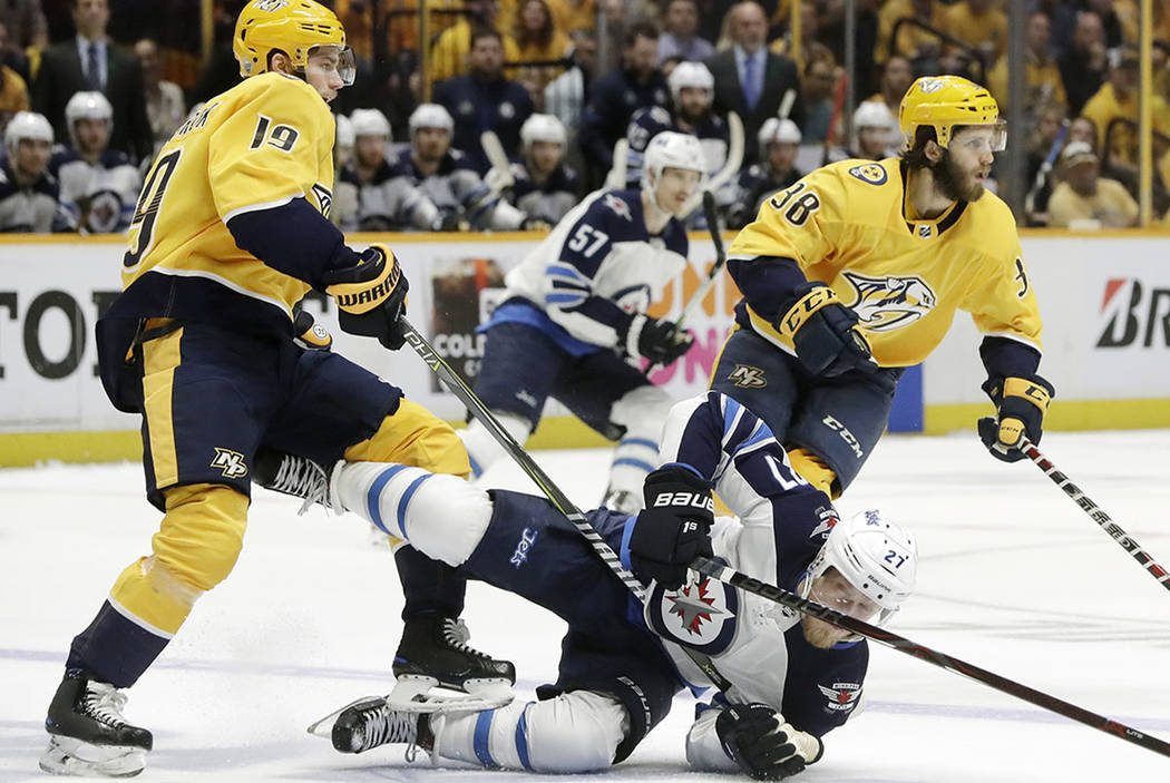 Winnipeg Jets left wing Nikolaj Ehlers (27), of Denmark, falls to the ice as he chases the puck with Nashville Predators center Calle Jarnkrok (19), of Sweden, and right wing Ryan Hartman (38) dur ...