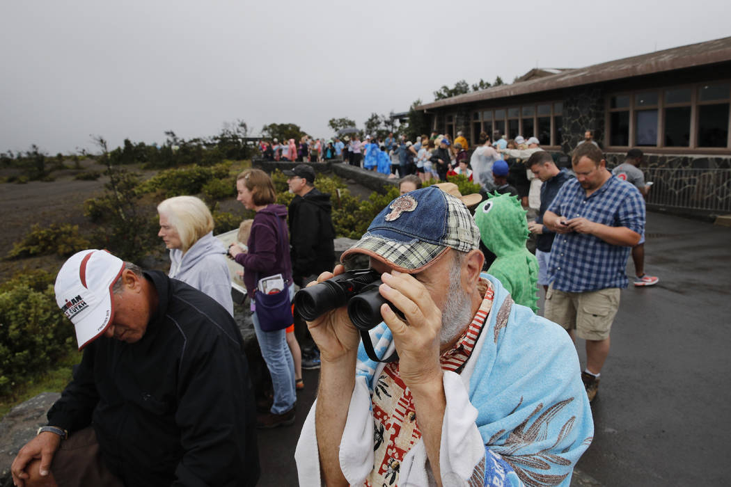 Visitors view Kilauea's summit crater outside the Jaggar Museum in Volcanoes National Park, Hawaii, Thursday, May 10, 2018. The park is closing Friday due to the threat of an explosive volcanic er ...