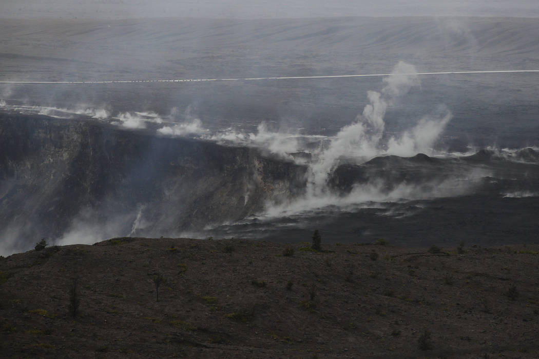 Steam and gas rise along the edge of Kilauea's summit crater in Volcanoes National Park, Hawaii, Thursday, May 10, 2018. The park is closing Friday due to the threat of an explosive volcanic erupt ...