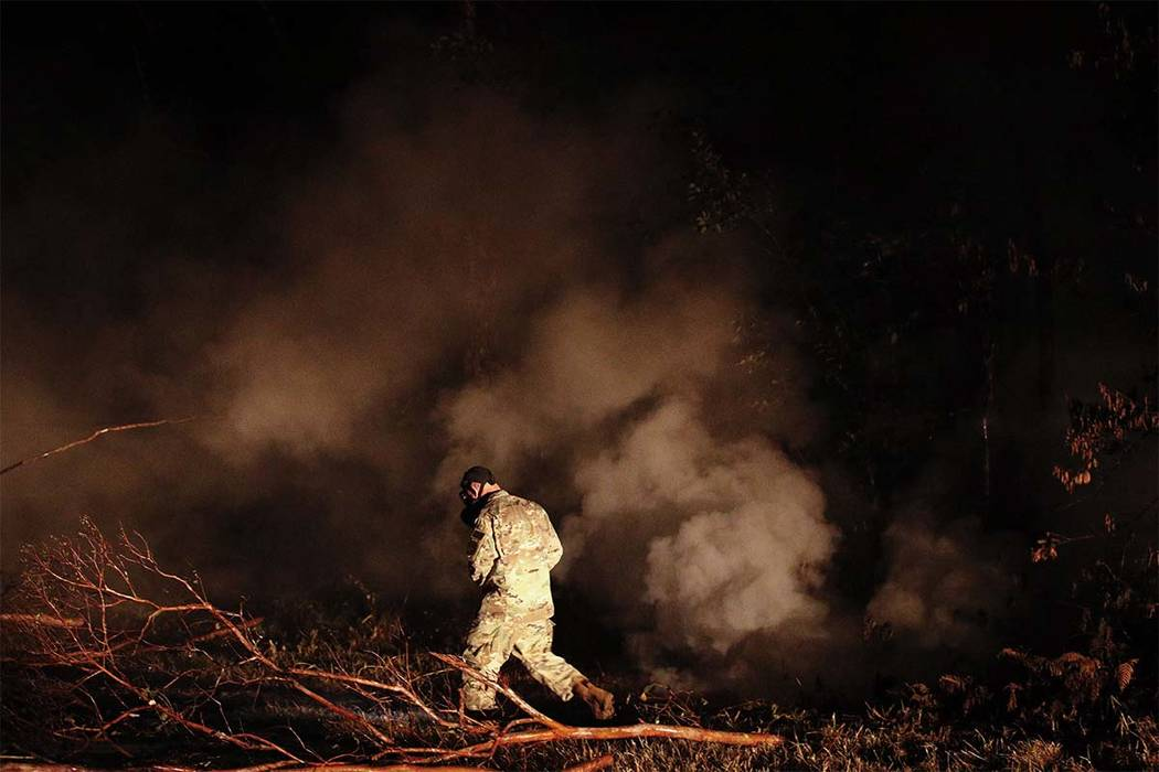 Sgt. 1st Class Carl Satterwaite, of the U.S. National Guard, tests air quality near cracks emitting volcanic gases from a lava flow in the Leilani Estates subdivision near Pahoa, Hawaii Thursday, ...