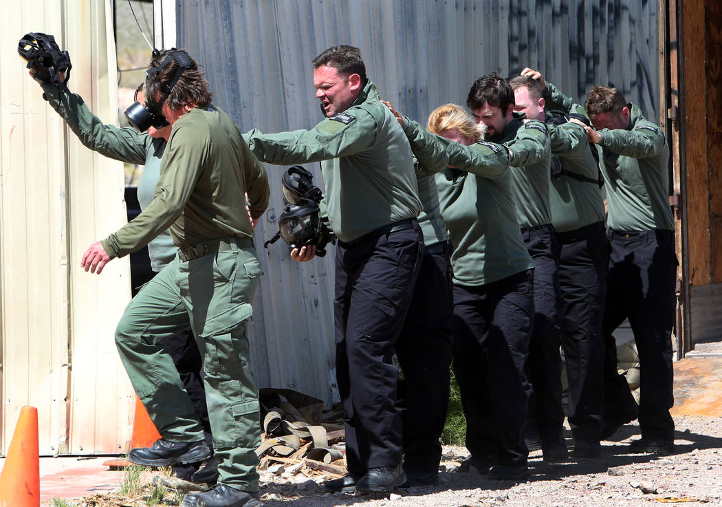 Paramedics from American Medical Response-Las Vegas gasp for fresh air as they exit the gas chamber after being exposed to CS tear gas during field training exercises on Friday, May 11, 2018, in B ...