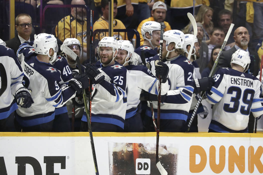 Winnipeg Jets players celebrate after a goal against the Nashville Predators late in the third period in Game 7 of an NHL hockey second-round playoff series Thursday, May 10, 2018, in Nashville, T ...