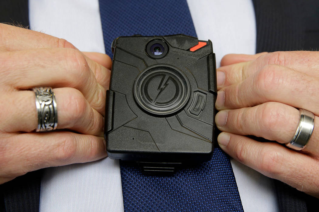 In this Feb. 19, 2015 file photo, Steve Tuttle, vice president of communications for Taser International, demonstrates one of the company's body cameras during a company-sponsored conference at th ...