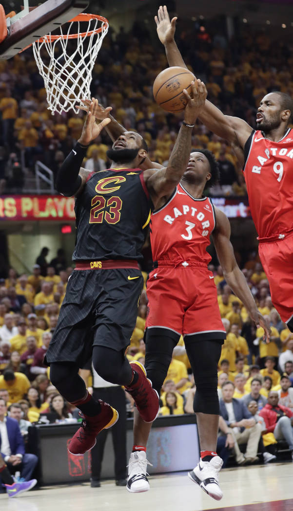 Cleveland Cavaliers' LeBron James (23) goes up to shoot against Toronto Raptors' Serge Ibaka (9), from Republic of Congo, and OG Anunoby (3) in the first half of Game 4 of an NBA basketball second ...