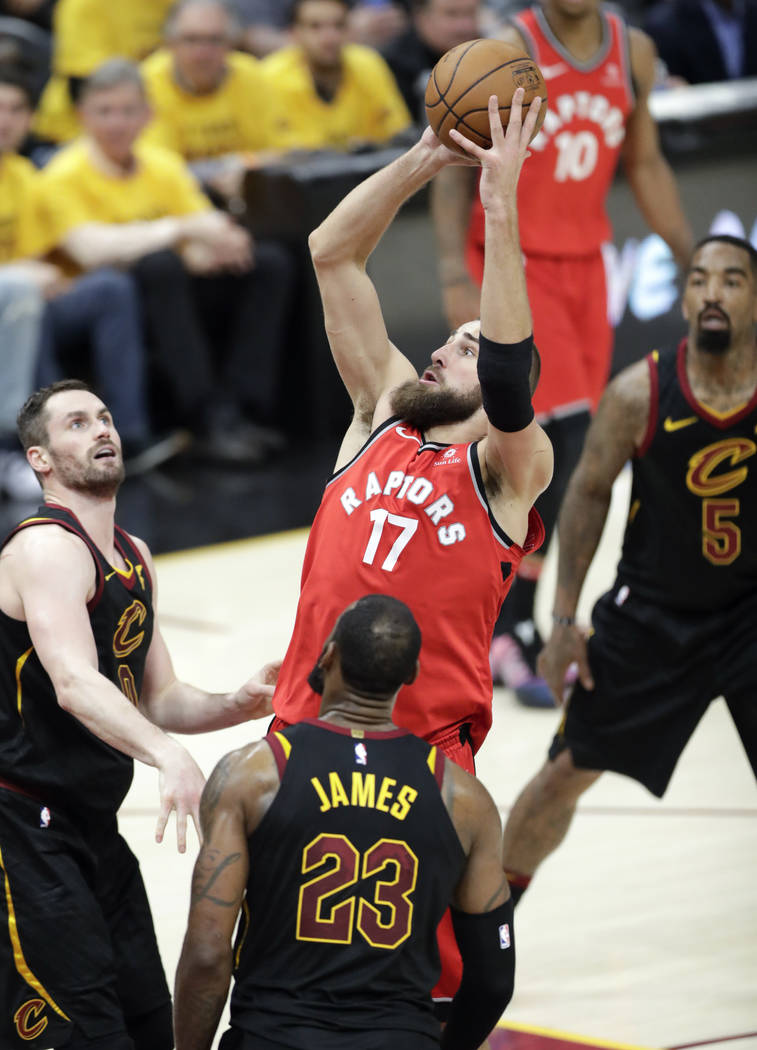 Toronto Raptors' Jonas Valanciunas (17), from Lithuania, shoots between Cleveland Cavaliers' Kevin Love, left, LeBron James (23) and JR Smith (5) in the second half of Game 4 of an NBA basketball ...