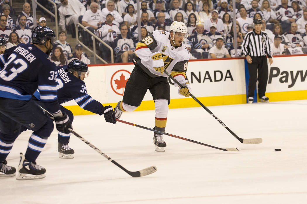 Vegas Golden Knights defenseman Nate Schmidt (88) is pressured by Winnipeg Jets defenseman Toby Enstrom (39) during the first period in Game 1 of an NHL hockey third-round playoff series at the Be ...