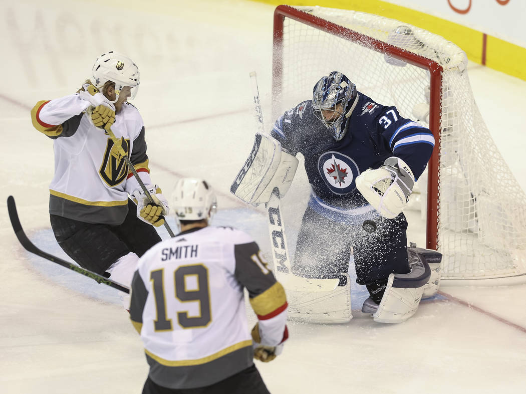 Winnipeg Jets goaltender Connor Hellebuyck (37) deflects an attempt by Vegas Golden Knights center William Karlsson (71) as Knights right wing Reilly Smith (19) looks on during the second period i ...