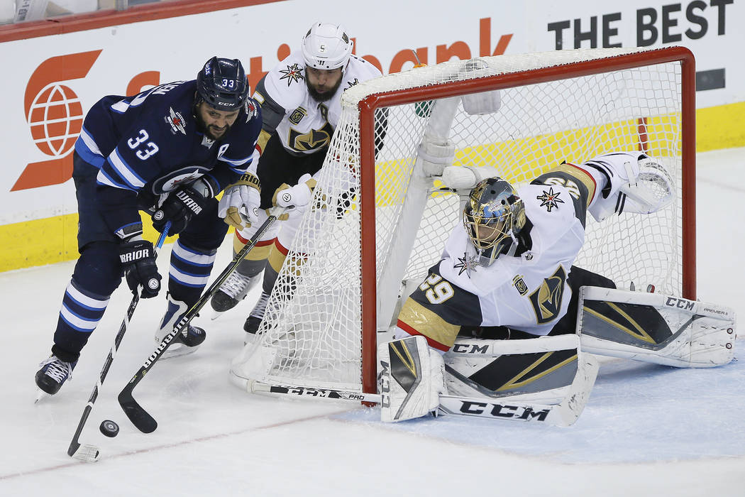 Winnipeg Jets' Dustin Byfuglien (33) attempts the wraparound on Vegas Golden Knights' Deryk Engelland (5) and goaltender Marc-Andre Fleury (29) during the third period of Game 1 of the NHL hockey ...