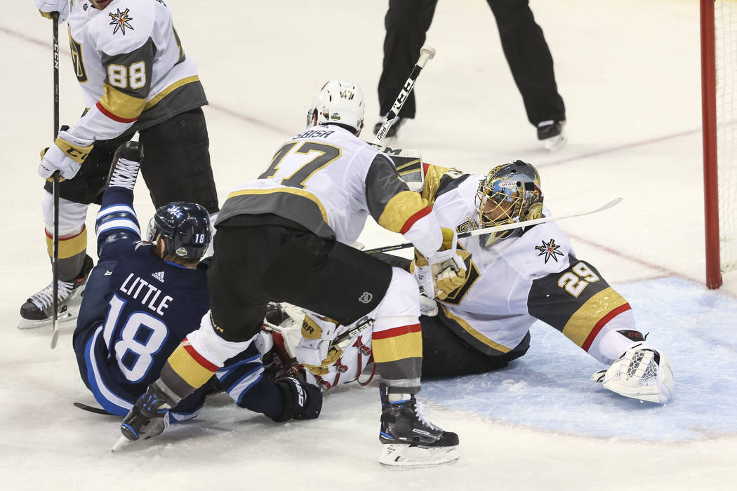 Vegas Golden Knights goaltender Marc-Andre Fleury (29) falls to the ice after colliding with Winnipeg Jets center Bryan Little (18) as Knights defensemen Nate Schmidt (88) and Luca Sbisa (47) defe ...