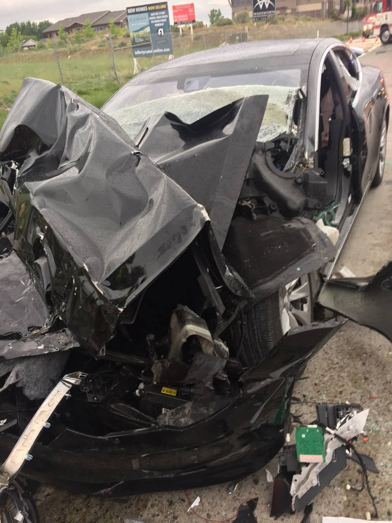 A traffic collision is seen involving a Tesla Model S sedan with a Fire Department mechanic truck stopped at a red light in South Jordan, Utah, on Friday. (South Jordan Police Department via AP)
