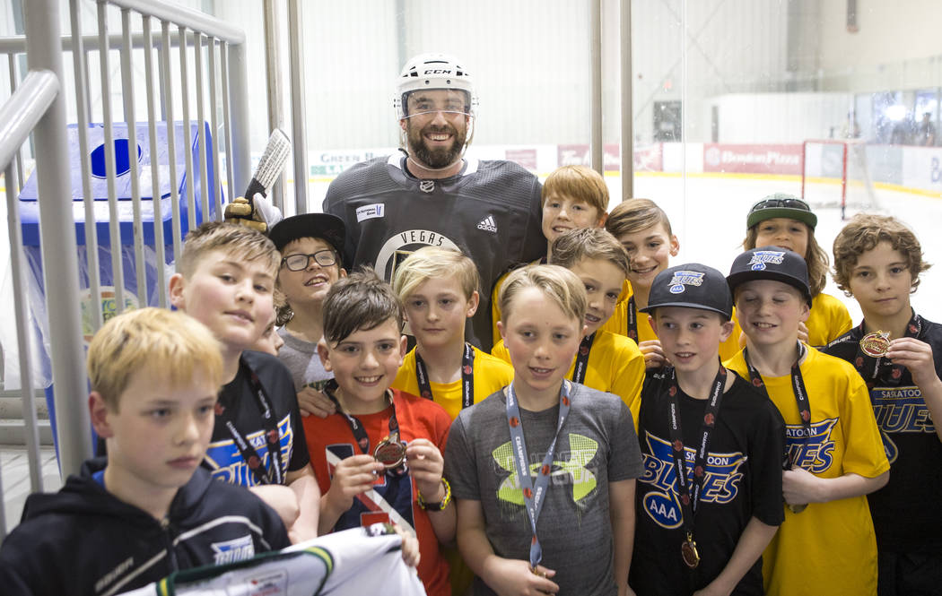 Vegas Golden Knights defenseman Brad Hunt, top center, poses with a group of youth hockey players after taking part in an optional team practice at the Bell MTS Iceplex in Winnipeg, Canada on Sund ...
