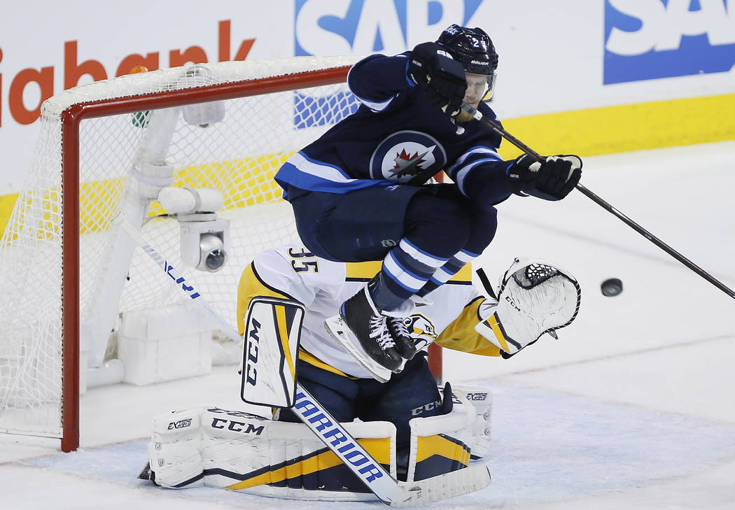 Winnipeg Jets' Nikolaj Ehlers (27) attempts to deflect the puck past Nashville Predators goaltender Pekka Rinne (35) during the third period of Game 4 of an NHL hockey second-round playoff series ...