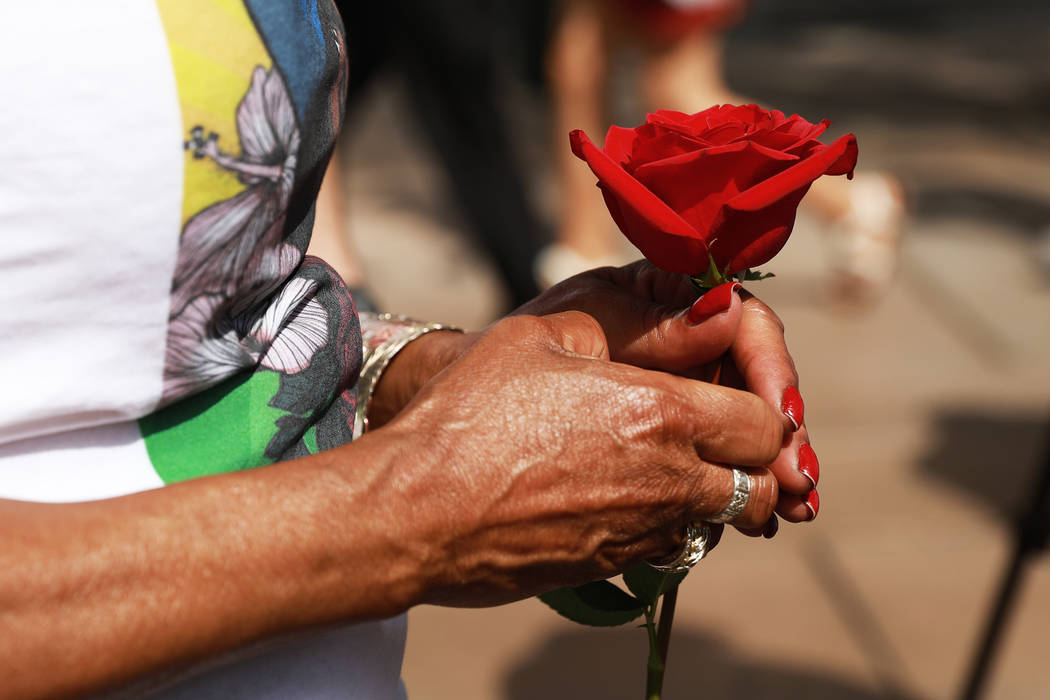 Trinita Farmer, whose son Ta­shii Brown died in th­e custody of the Metr­opolitan Police Depar­tment a year ago, holds a rose during a vigil for her son in front of the Bellagio in Las Vegas ...