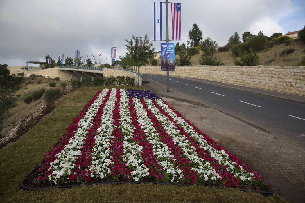 Flowers decorated as an American flag are seen on a road leading to the US Embassy compound ahead the official opening in Jerusalem, Sunday, May 13, 2018. On Monday, the United States moves its em ...