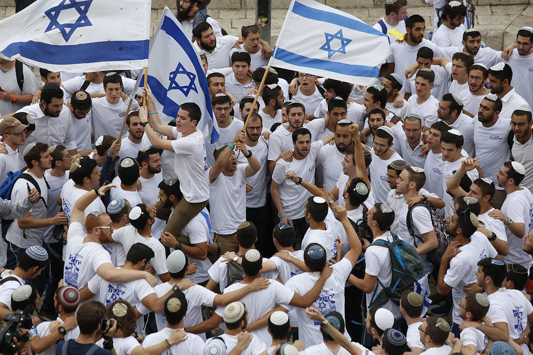 Israeli youths wave national flags outside the Old City's Damascus Gate, in Jerusalem, Sunday, May 13, 2018. Israel is marking the 51tst anniversary of its capture of east Jerusalem in the 1967 Mi ...