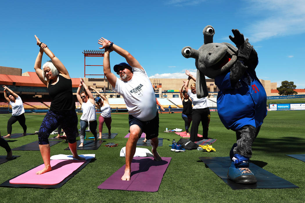 Cosmo, the Las Vegas 51s' mascot, does yoga with Chuck Johnson, general manager of the 51s, center, and his wife Andrea during a Yoga on the Field event at Cashman Field in Las Vegas on Sunday, Ma ...