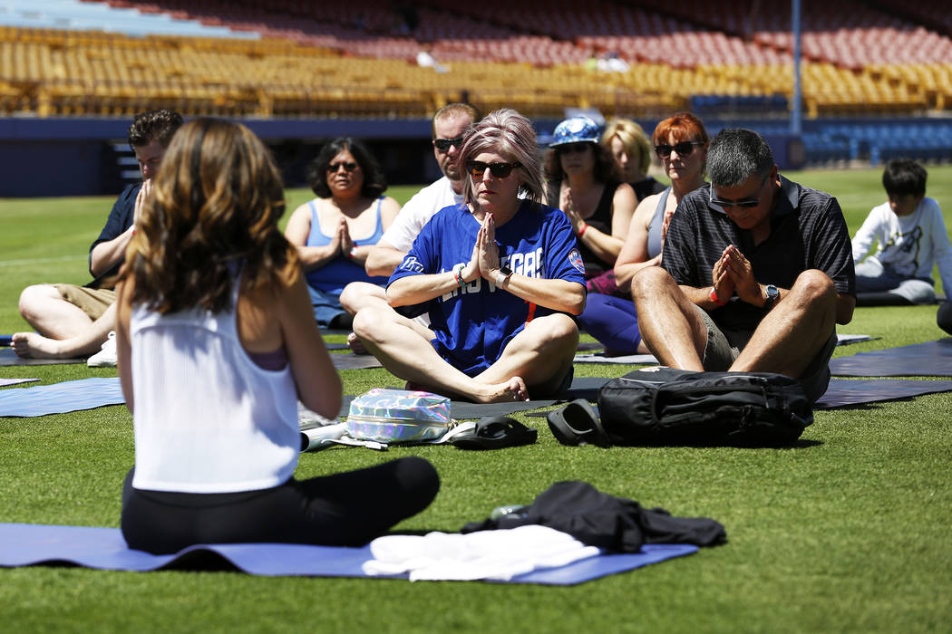 Joanne Martelli, center, and her fianc Tom Hopkins, both of Pheonix, participate in a Yoga on the Field event at Cashman Field in Las Vegas on Sunday, May 13, 2018. Andrea Cornejo Las Vegas Review ...
