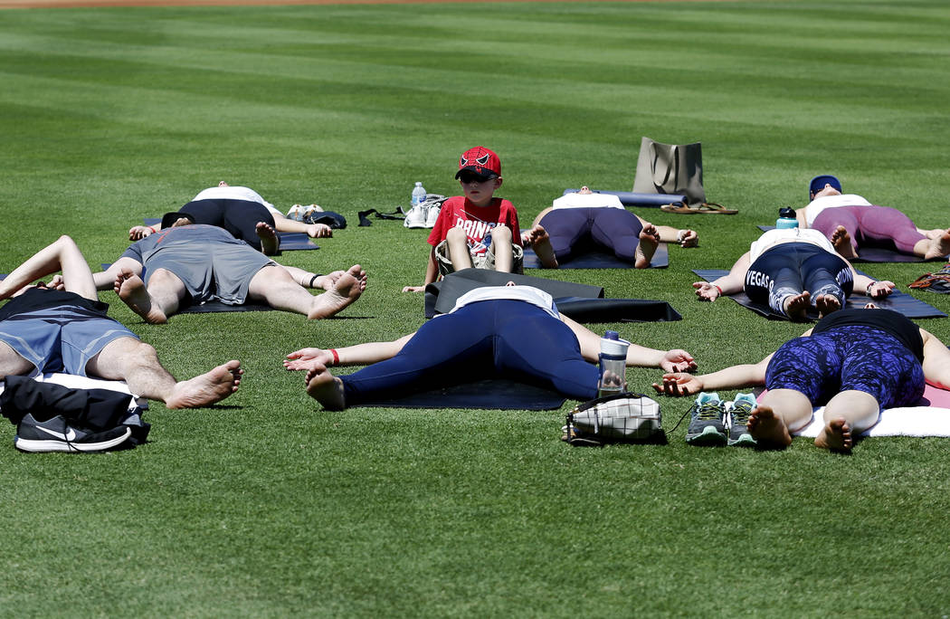 Attendees do yoga during a Yoga on the Field event at Cashman Field in Las Vegas on Sunday, May 13, 2018. Andrea Cornejo Las Vegas Review-Journal @dreacornejo