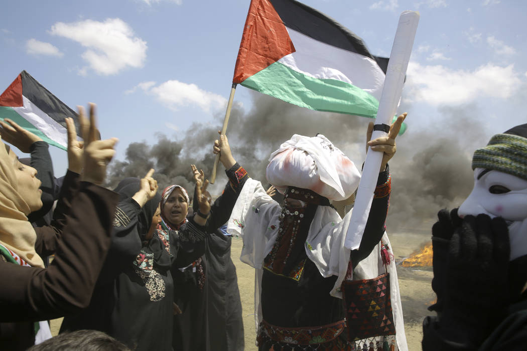 Palestinian women wave national flags and chant slogans near the Israeli border fence, east of Khan Younis, in the Gaza Strip, Monday, May 14, 2018. Thousands of Palestinians are protesting near G ...