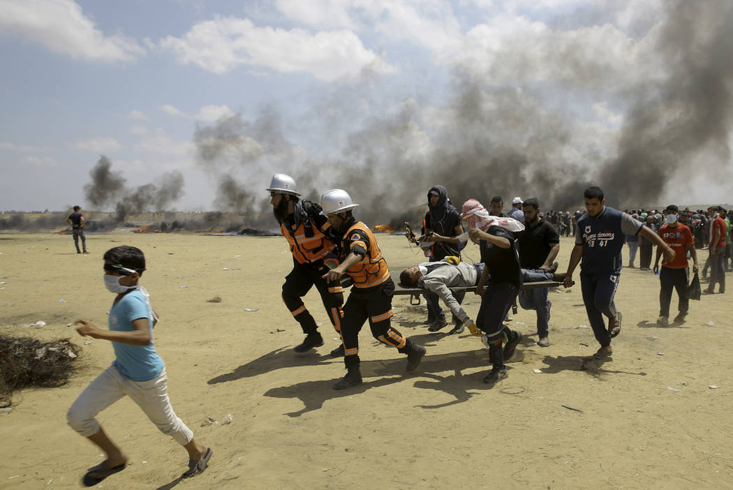 Palestinian medics and protesters evacuate a wounded youth during a protest at the Gaza Strip's border with Israel, east of Khan Younis, Gaza Strip, Monday, May 14, 2018. Thousands of Palestinians ...