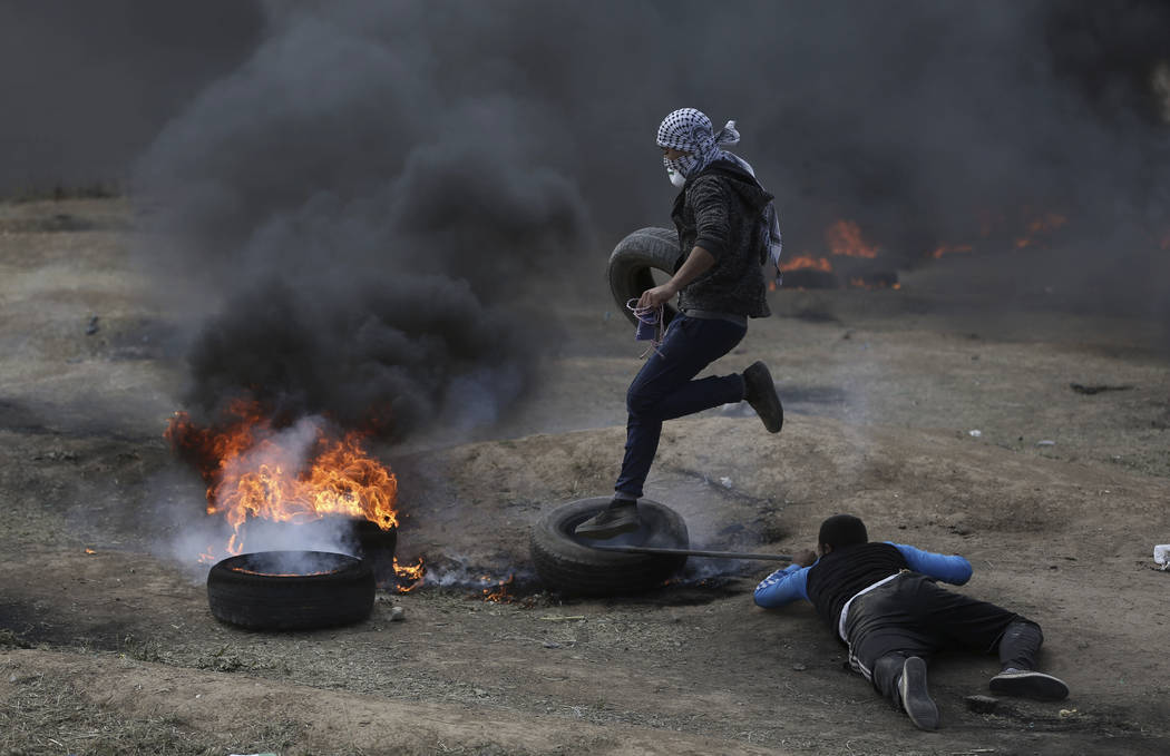 Palestinian protesters burn tires during a protest on the Gaza Strip's border with Israel, Monday, May 14, 2018. Thousands of Palestinians are protesting near Gaza's border with Israel, as Israel ...