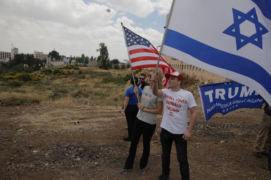 Israelis hold American and Israeli flags with the new U.S. embassy in the background in Jerusalem, Monday, May 14, 2018. Israel prepared for the festive inauguration of a new U.S. Embassy in conte ...