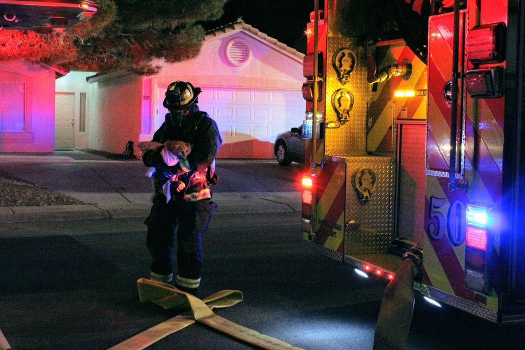 A North Las Vegas firefighter carries a cat out of a home Monday morning after a fire at 5920 N. Vista Del Rancho Way. (Max Michor/Las Vegas Review-Journal)