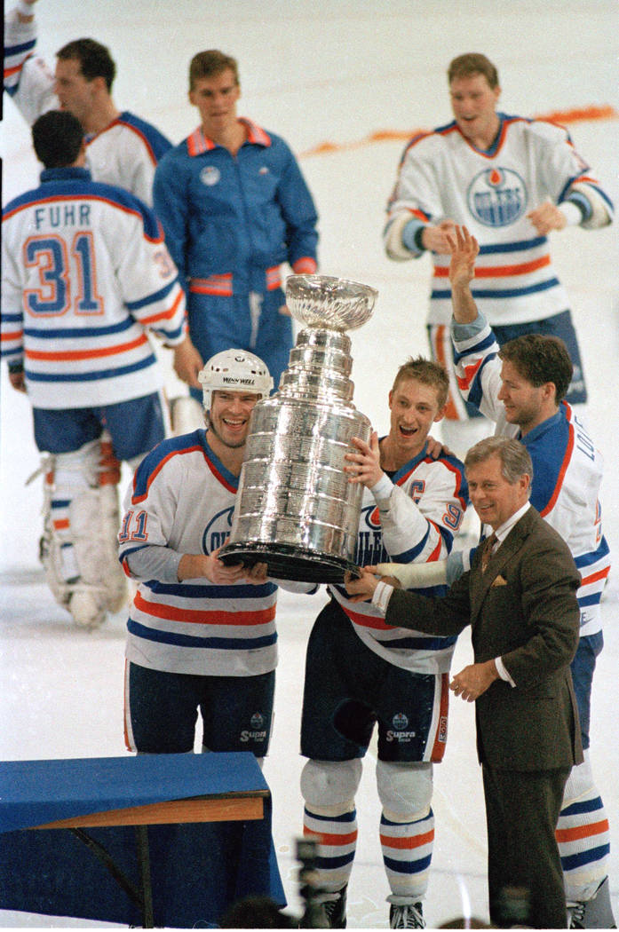 Edmonton Oilers team captain Wayne Gretzky, right, and Mark Messier hold up the Stanley Cup trophy following the team's 6-3 win over the Boston Bruins in the Stanley Cup hockey finals in Edmonton, ...