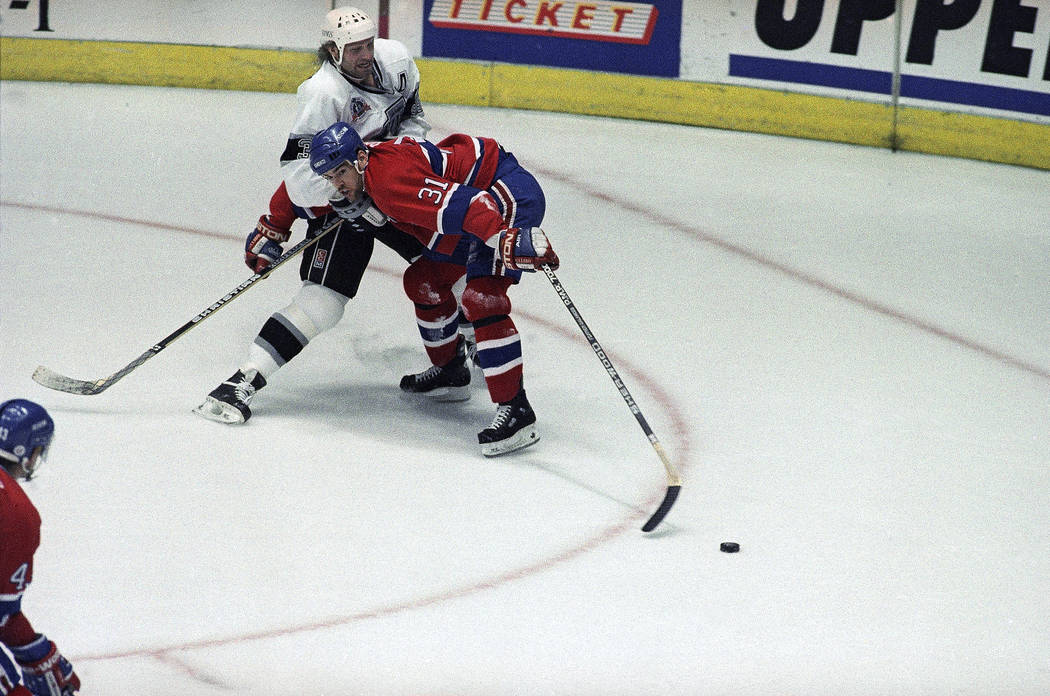 Montreal Canadiens right winger Ed Ronan (31) manages to lunge for the puck despite being hung up by the Los Angeles Kings Marty McSorley (33) in the first period of game 3 of the Stanley Cup cham ...