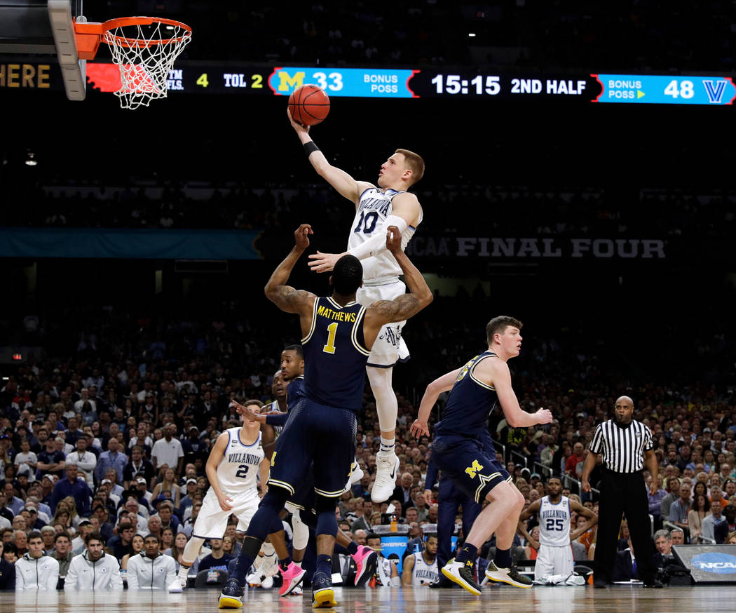 Villanova guard Donte DiVincenzo drives to the basket over Michigan guard Charles Matthews (1) during the second half in the championship game of the Final Four NCAA college basketball tournament, ...