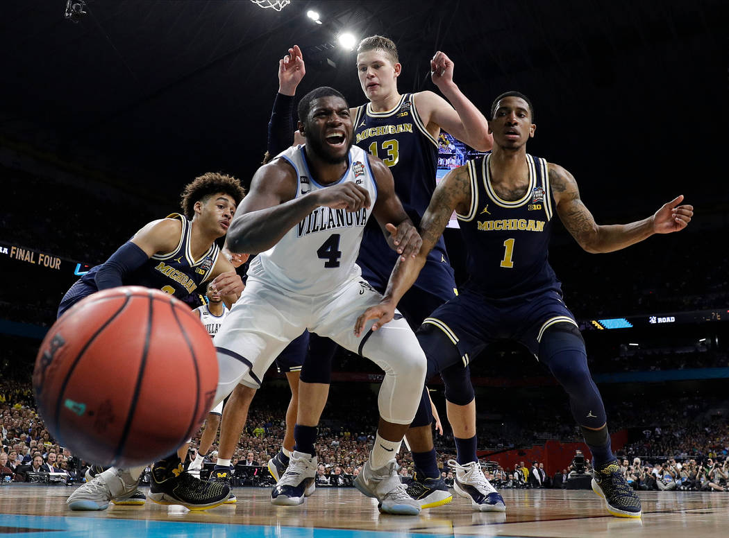 Villanova's Eric Paschall (4) reacts as he loses the control of the ball against Michigan's Moritz Wagner (13) and Charles Matthews (1) during the first half in the championship game of the Final ...
