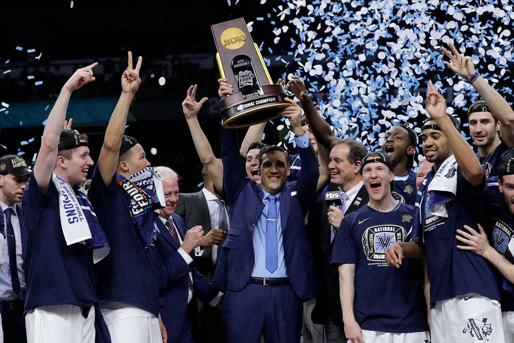 Villanova head coach Jay Wright, center, celebrates with his team after beating Michigan 79-62 in the championship game of the Final Four NCAA college basketball tournament, Monday, April 2, 2018, ...