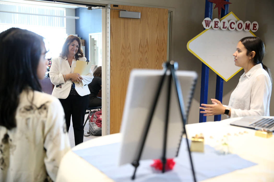 East Career and Technical Academy principal Darlin Delgado, center, looks on during a presentation by Aurora Osuna, 16, right, and Kirsten Nicholas, marketing and hospitality students, during a pr ...