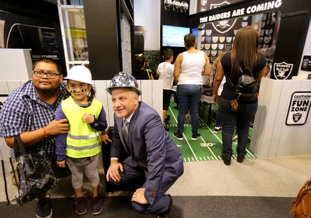 Marc Badain, the president of the Raiders, right, poses with Wendy Carranco, 5, and her father Omar Gervacio during the opening of the Raiders Kids Construction Zone Groundbreaking exhibit at Disc ...