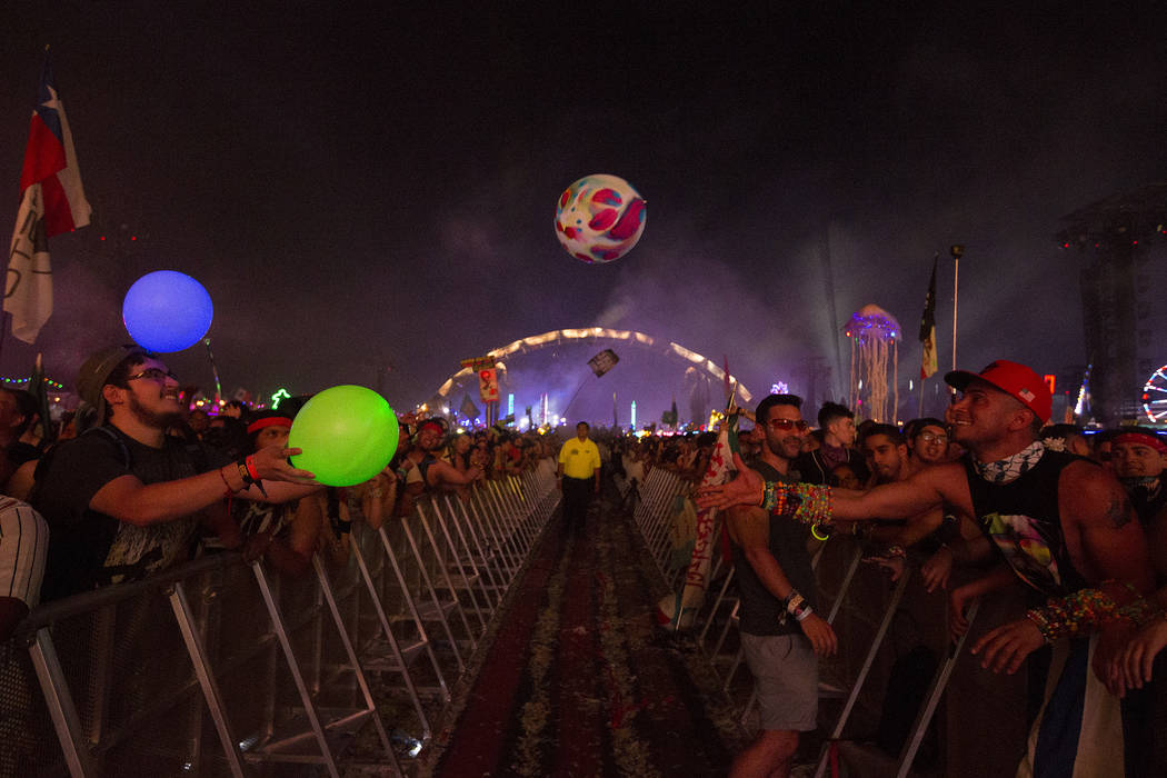 Juan Ignacio Ortiz Frutos, left, from Mexico and Leonard Romero Rodriguez, right, from Cuba exchange balloons during Tiesto's set at Kinetic Field on the second night of Electric Daisy Carnival at ...