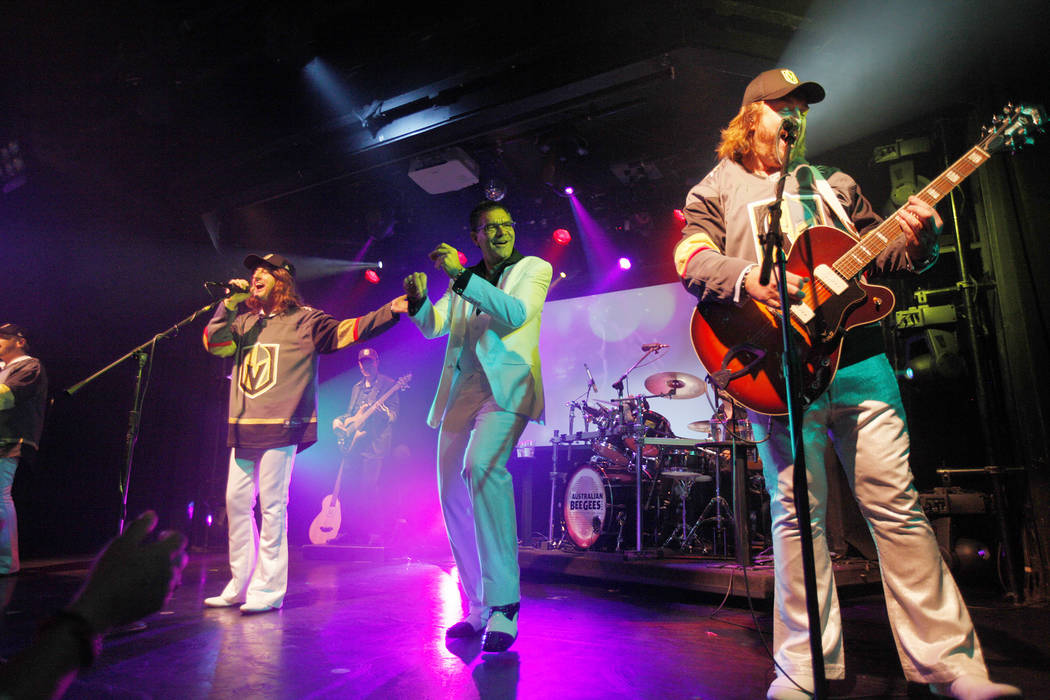 David Scott as Robin Gibb, left, Michael Clift as Barry Gibb of the Australian Bee Gees, a Bee Gee tribute band, perform as Review-Journal columnist John Katsilometes dances at the Thunder Showroo ...