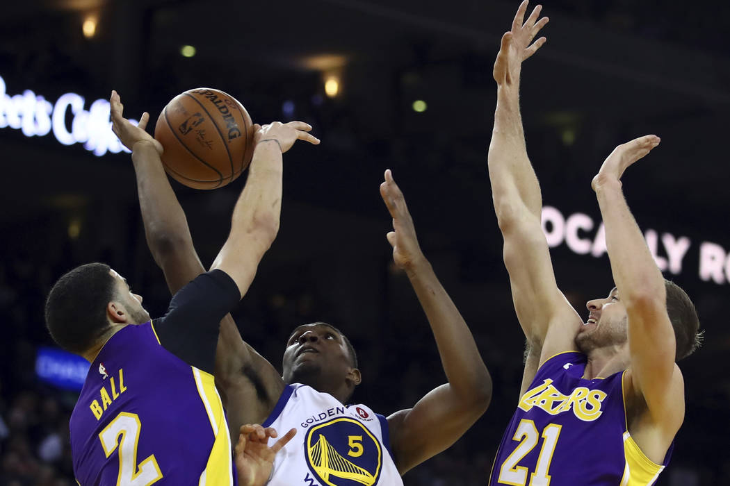 Golden State Warriors' Kevon Looney, center, is guarded by Los Angeles Lakers' Lonzo Ball (2) and Travis Wear (21) during the second half of an NBA basketball game Wednesday, March 14, 2018, in Oa ...
