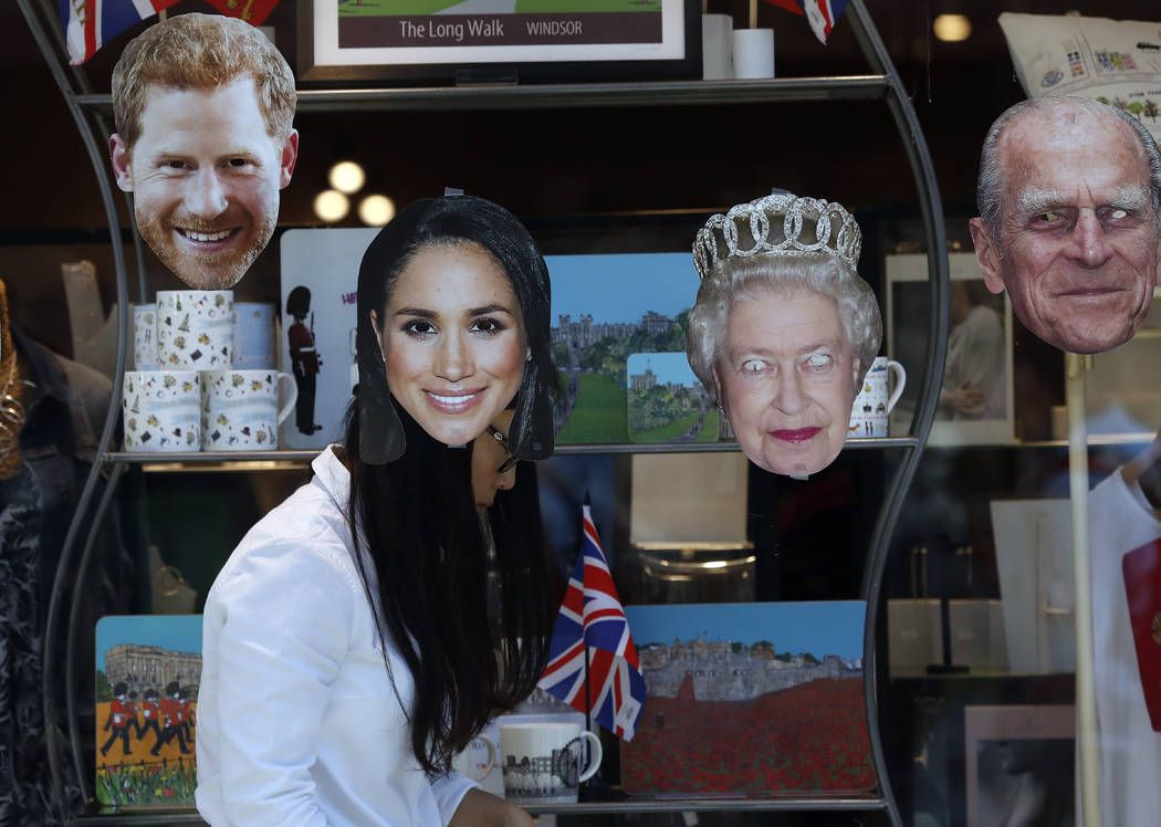 A shop assistant decorates a shop window in Windsor, England, Tuesday, May 15, 2018. Preparations continue in Windsor ahead of the royal wedding of Britain's Prince Harry and Meghan Markle Saturd ...