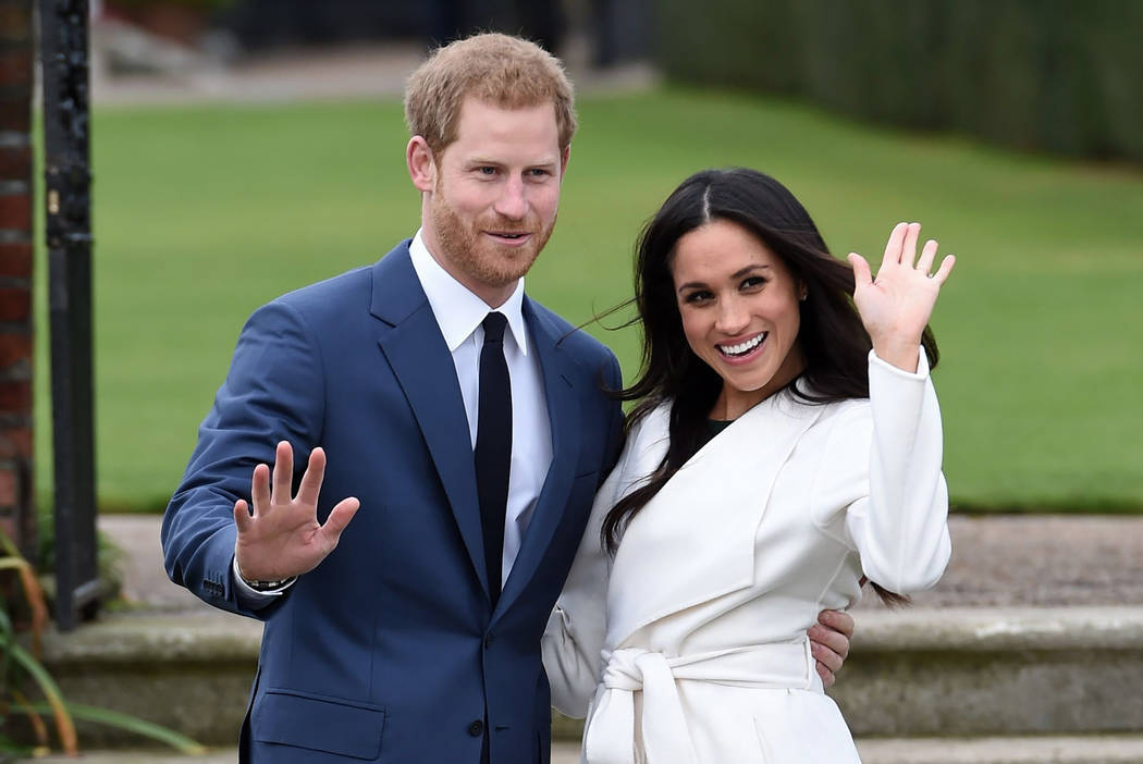 FILE - In this Nov. 27, 2017 file photo, Britain's Prince Harry and Meghan Markle pose for the media in the grounds of Kensington Palace in London, after announcing their engagement. The couple wi ...
