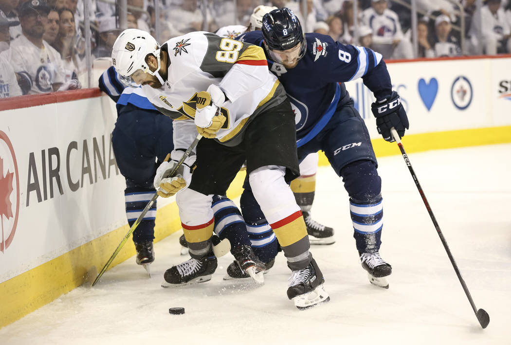 Vegas Golden Knights right wing Alex Tuch (89) keeps the puck away from Winnipeg Jets defenseman Jacob Trouba (8) during the second period in Game 2 of an NHL hockey third round playoff series at ...