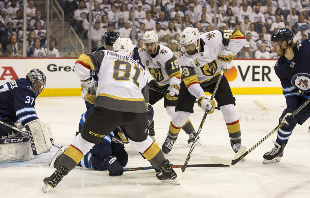 Vegas Golden Knights center Jonathan Marchessault (81), Reilly Smith (19) and Alex Tuch (89) look for the rebound against the Winnipeg Jets during the second period in Game 2 of an NHL hockey thir ...