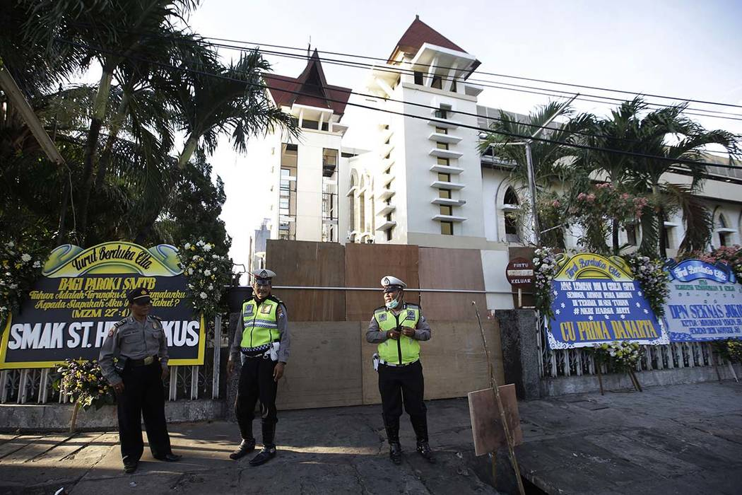 Police officers stand guard outside one of the churches attacked on Sunday, in Surabaya, East Java, Indonesia, Monday, May 14, 2018. The flurry of bombings raised concerns that previously beaten-d ...