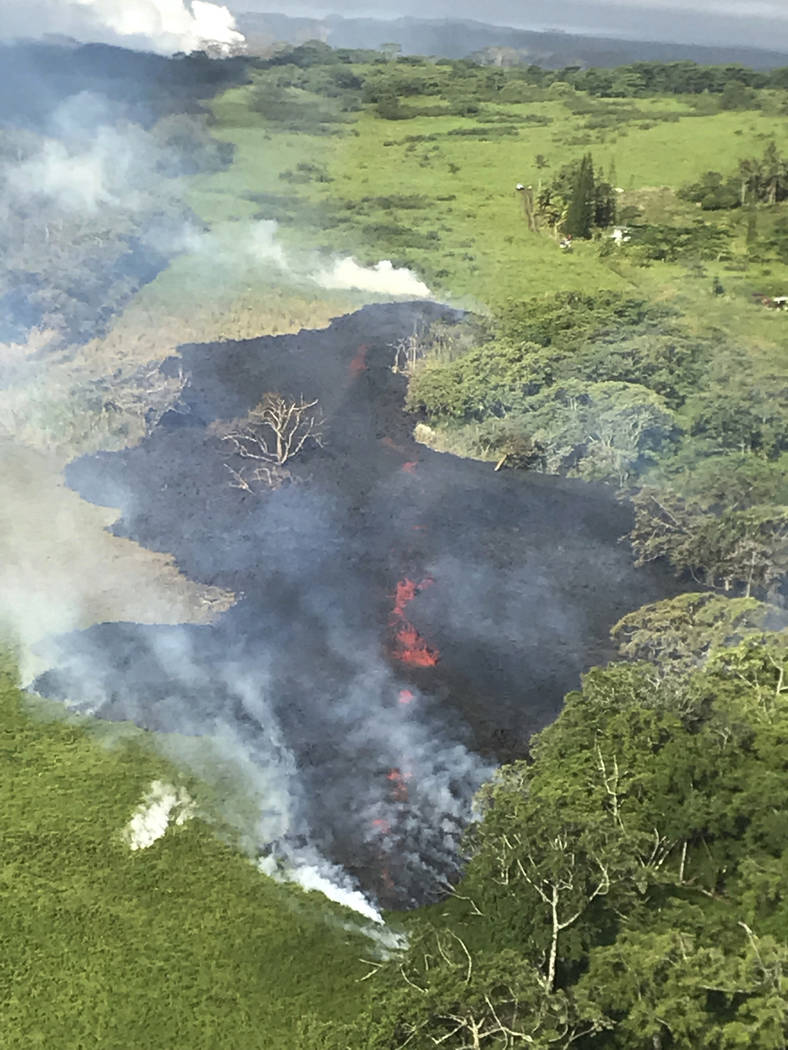 In this May 13, 2018 photo released by the U.S. Geological Survey, gases rise from a fissure near Pahoa, Hawaii. The new fissure in Hawaii's Puna District sent gases and lava exploding into the ai ...