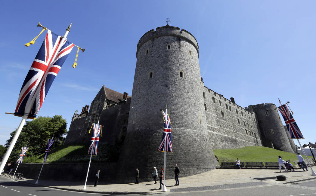 Flags fly in front of the castle in Windsor, England, Monday, May 14, 2018. Preparations are being made in the town ahead of the wedding of Britain's Prince Harry and Meghan Markle that will take ...